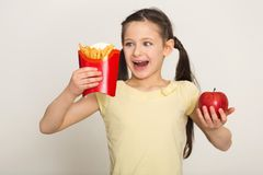 Happy little girl holding a bag of fries and apple stock photo