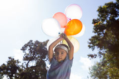 Happy little girl holding balloons Royalty Free Stock Image