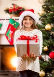 Happy little girl holding big Christmas gift box Royalty Free Stock Photography