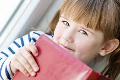Happy little girl holding a book Royalty Free Stock Image