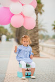 Happy little girl holding a bunch of balloons Royalty Free Stock Image