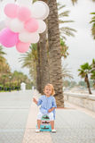 Happy little girl holding a bunch of balloons Royalty Free Stock Photos