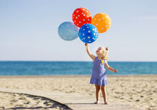 Happy little girl holding bunch of colorful air balloons at the Royalty Free Stock Images