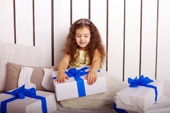 Happy little girl holding Christmas gifts. Royalty Free Stock Images