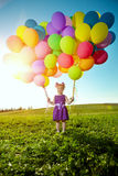 Happy little girl holding colorful balloons. Child playing on a Stock Photo