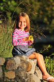 Happy little girl holding a flower stock photography