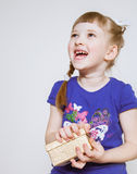 Happy little girl holding gift box stock photography
