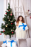 Happy little girl holding gifts near Christmas tree. Stock Photo