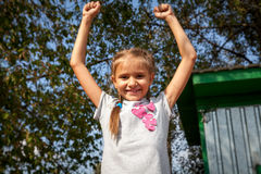 Happy little girl holding hands up at park at sunny day Royalty Free Stock Images