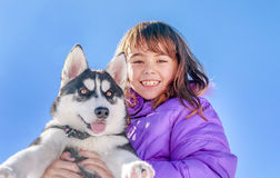 Happy little girl holding her puppy dog husky Stock Photos