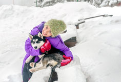Happy little girl holding her puppy dog husky on the snow Stock Photography