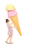 Happy little girl holding a huge ice cream. Isolated on white background Royalty Free Stock Image