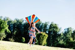 Happy little girl holding a kite and running Stock Photos