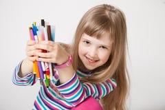 Happy little girl holding many felt-tip pens Stock Photo