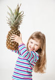 Happy little girl holding a pineapple Stock Photos