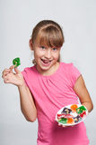 Happy little girl holding a plate with colorful jelly candies Royalty Free Stock Photos