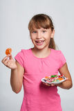 Happy little girl holding a plate with colorful jelly candies Stock Photography