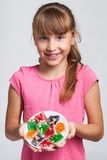 Happy little girl holding a plate with colorful jelly candies Royalty Free Stock Image