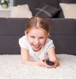 Little girl watching TV. Happy little girl holding a remote control Royalty Free Stock Photos