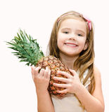 Happy little girl holding ripe whole pineapple Stock Photo