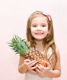 Happy little girl holding ripe whole pineapple Royalty Free Stock Image