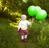Happy little girl holding three green ball stock photography
