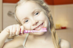 Happy little girl holding toothbrush and smiling  indoors Stock Photography