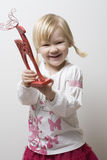 Happy little girl holding toy reindeer. Stock Photography