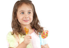 Happy little girl holding two candies in her hands Stock Images