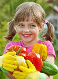 Happy little girl holding vegetables Stock Image
