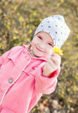 Happy little girl holding a yellow flower Stock Image