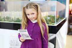Happy little girl holds booklet and stands Stock Photography