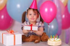 Happy little girl holds a gift on her Birthday. Happy little girl in the cap holds a gift on her Birthday Stock Images