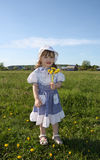 Happy little girl holds yellow dandelions Royalty Free Stock Photo