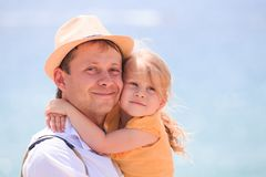 Happy little girl hugging father. Cheerful young man with child. Happy little girl hugging father. Cheerful young men with child close-up on sea background royalty free stock images