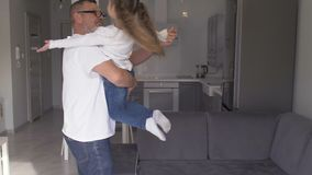 Happy little girl hugging grandfather playfully jumping into grandad`s arms, having fun enjoying weekend with