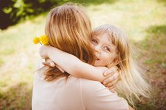 Happy little girl hugging her mother in sunny day. And smile, family life royalty free stock photo