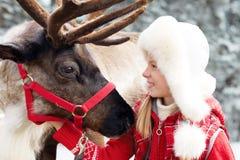 Happy little girl hugging her reindeer. Royalty Free Stock Image