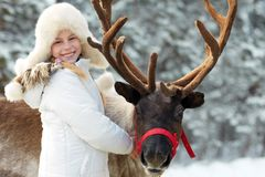 Winter playtime.Happy little girl hugging her reindeer. Royalty Free Stock Image