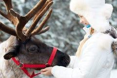 Happy little girl hugging her reindeer. Winter playtime. Royalty Free Stock Photo