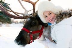 Happy little girl hugging her reindeer. Winter playtime. Stock Photo