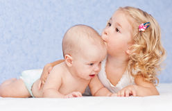 Happy little girl hugging kissing brother. Happy little girl hugging kissing his brother on a blue background royalty free stock photography