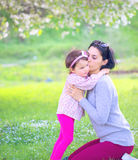 Happy little girl hugging and kissing her mother Royalty Free Stock Photos