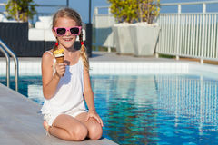 Happy little girl with ice cream sitting near a swimming pool at Stock Photos