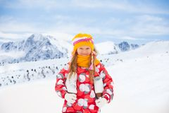 Happy little girl with ice skates. Close portrait of happy smiling little Caucasian girls standing outside in snow with ice-skates with mountain on background Stock Photography