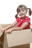 Happy little girl inside a paper box. At home Stock Photography