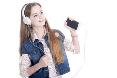 Happy little girl in jeans jacket listening music with smartphon stock photography