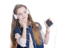Happy little girl in jeans jacket listening music with smartphone on white background royalty free stock image