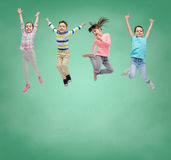 Happy little girl jumping in air over school board. School, education, childhood, freedom and people concept - happy little girl jumping in air over green school Stock Photos