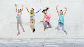 Happy little girl jumping in air on street Royalty Free Stock Images